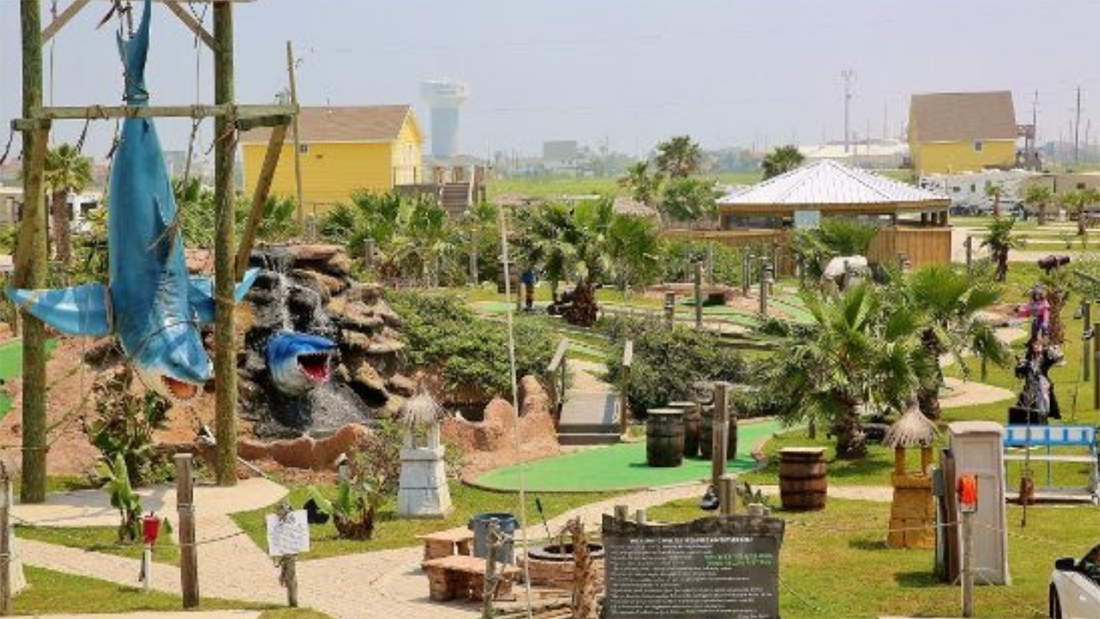 Sharks and palm trees add atmosphere to a miniature golf course in Jamaica RV Resort.