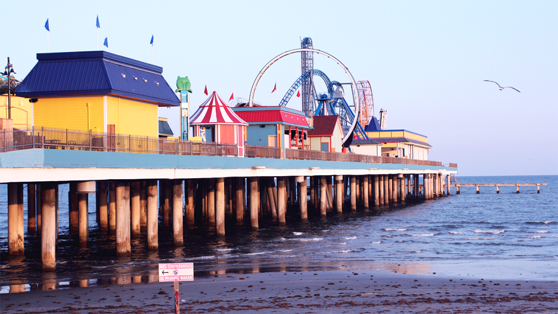 Colorful buildings and amusement park rides sit on an ocean pier in Galveston, Texas.