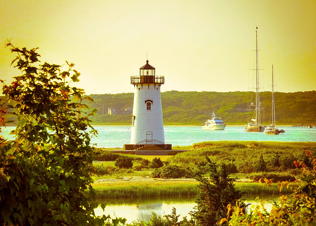 A white lighthouse towers over an inlet with two sailboats and one cruising boat on the water in the background.