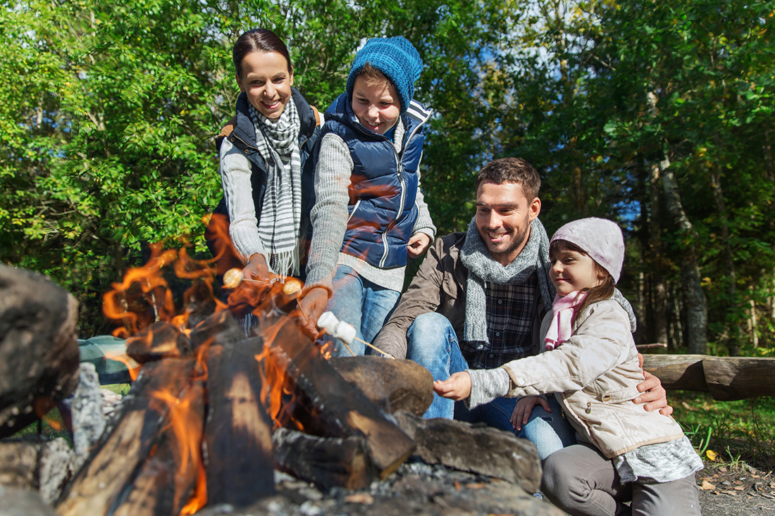 A family of four gathering around a campfire to roast marshmallows.