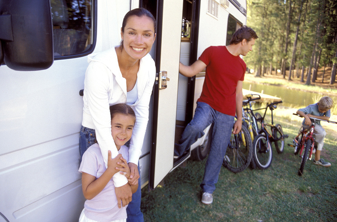 A family relaxing around their motorhome.