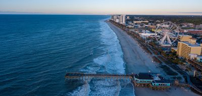 An aerial shot of a beach with pier jutting into ocean and buildings and attractions inland from the sand at Myrtle Beach.