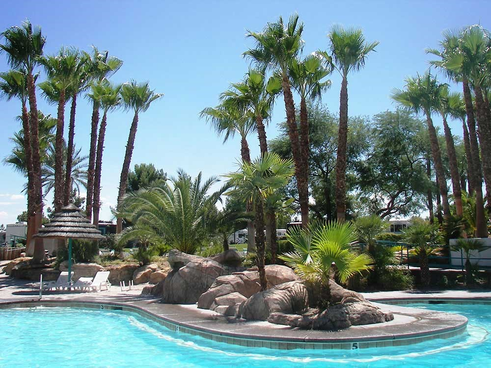 Palm trees and boulders form a tropical landscaping around the aqua-blue waters of the Oasis Las Vegas RV resort pool.