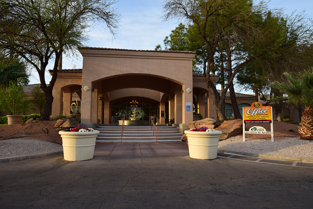 Flanked by large planters that grow flowers, a stairway leads to the adobe-style entrance to the office complex of Oasis Las Vegas RV Resort.