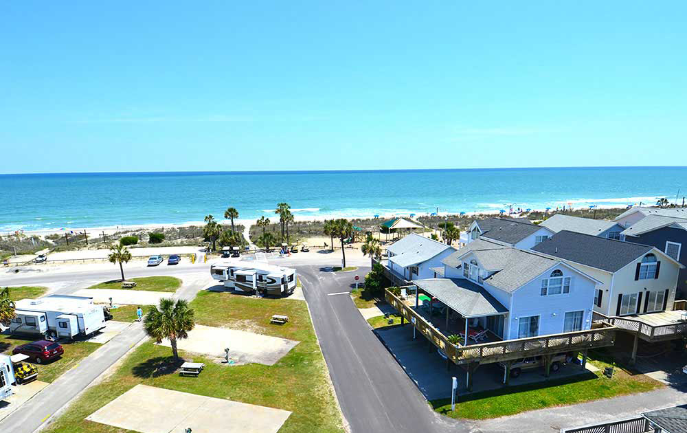 An RV Resort with green lawns, concrete pads and trails faces the Atlantic coast at Ocean Lakes Family Campground.