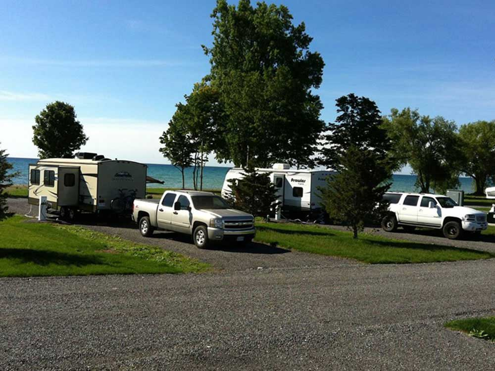 Travel trailers and trucks occupy campsites near the turquoise water of Lake Ontario at Quinte's Isle Campark.