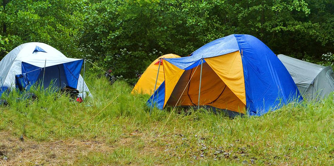Tents camped in a muddy field in the rain.