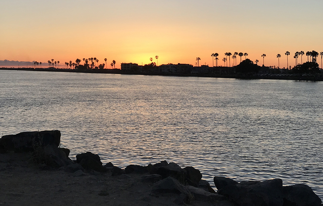 A rocky jetty Sunset over San Diego's Mission Bay with palm trees on the horizon.