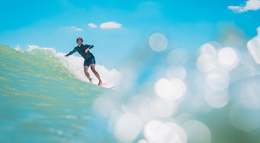 A surfer in a spring suit rides a wave with turquoise water on Texas's Gulf Coast.