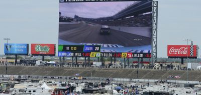 Large screen above Texas Motor Speedway showing NASCAR racing, with RVs in center