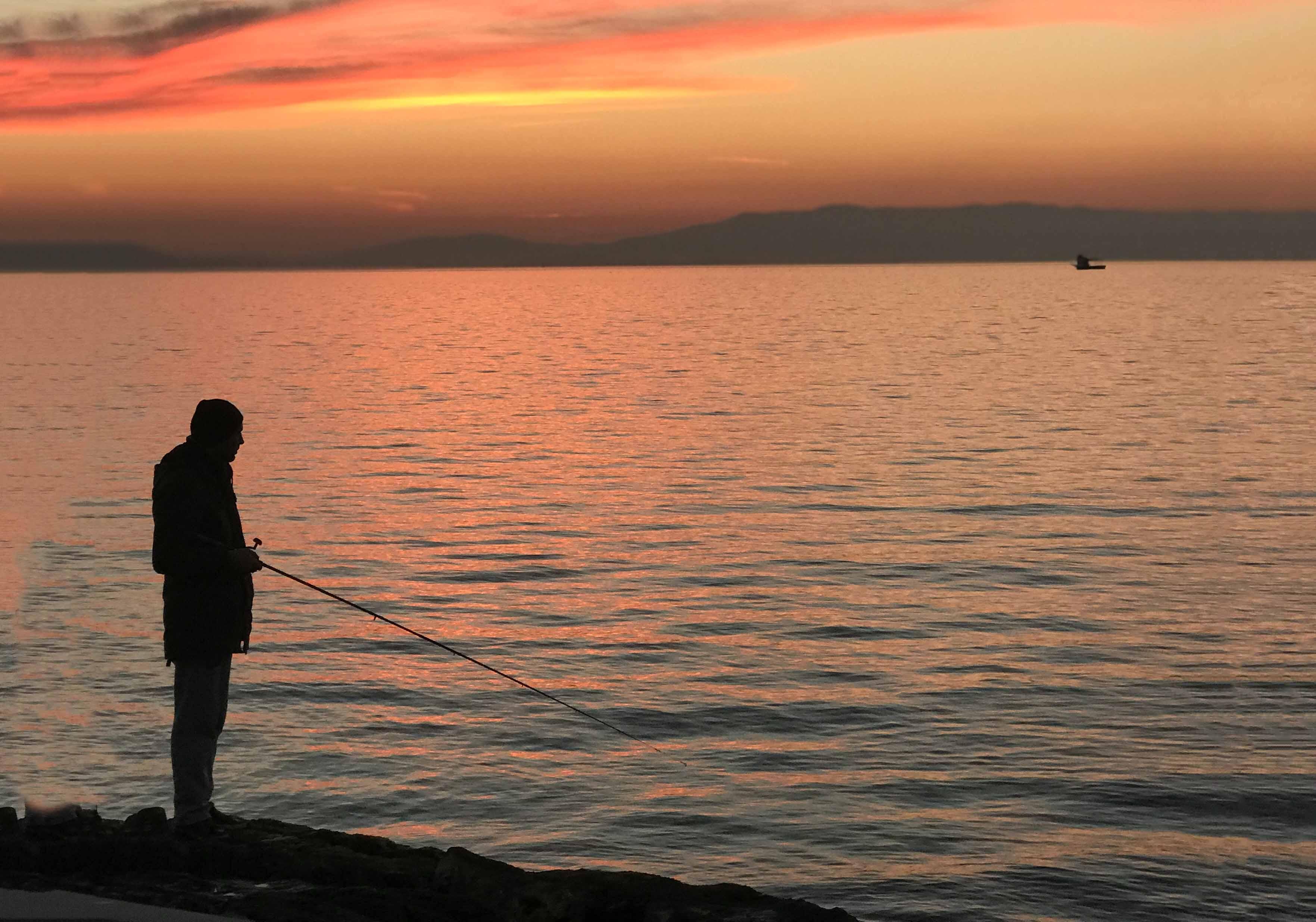 Fishing during dusk on a vast lake.