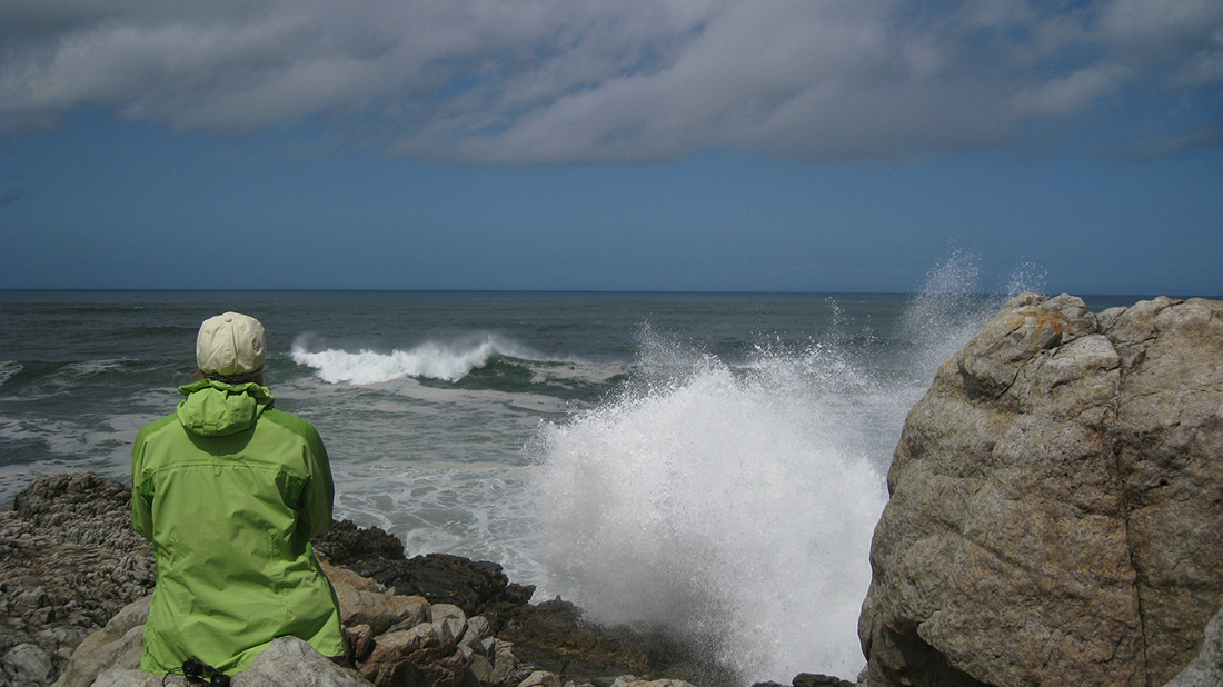 Camper in a green jacket enjoys watching the surf.