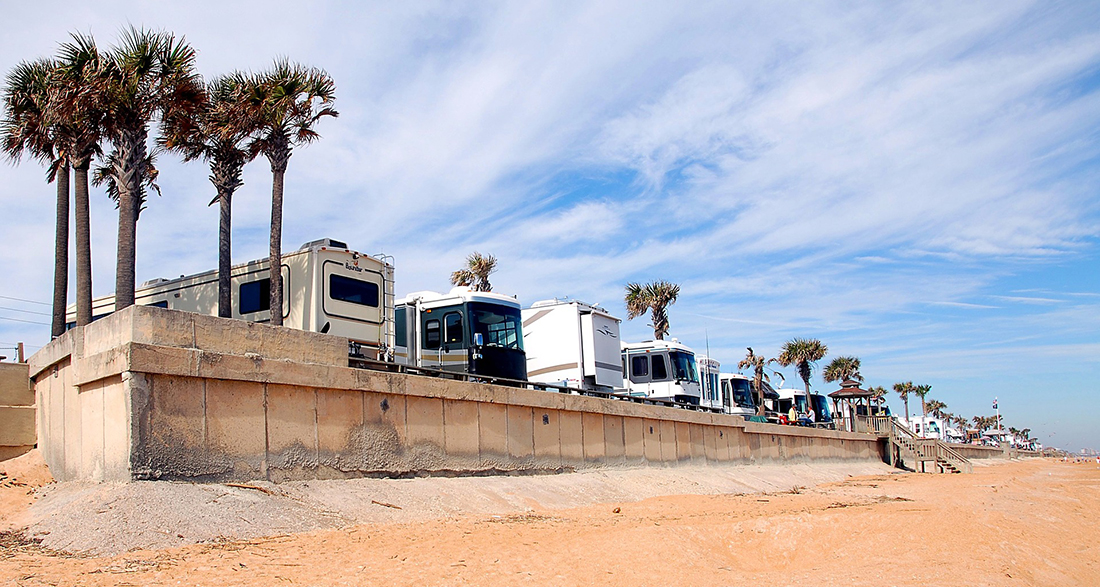 Motorhomes line the beach on a coastal campground.