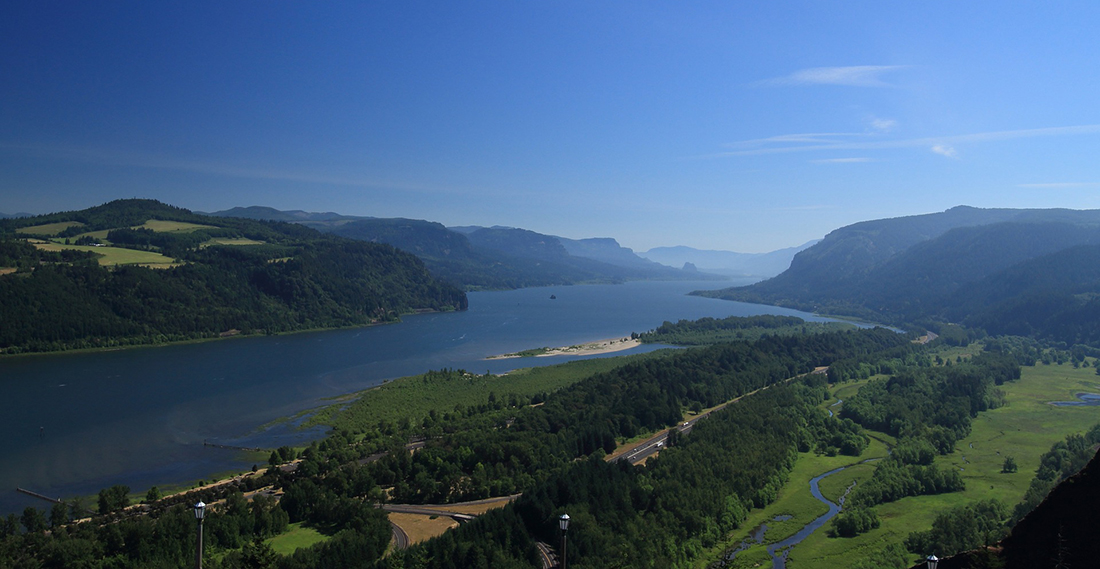 The Columbia River surrounded by bluffs on both side under a blue sky at the Oregon/Washington border.
