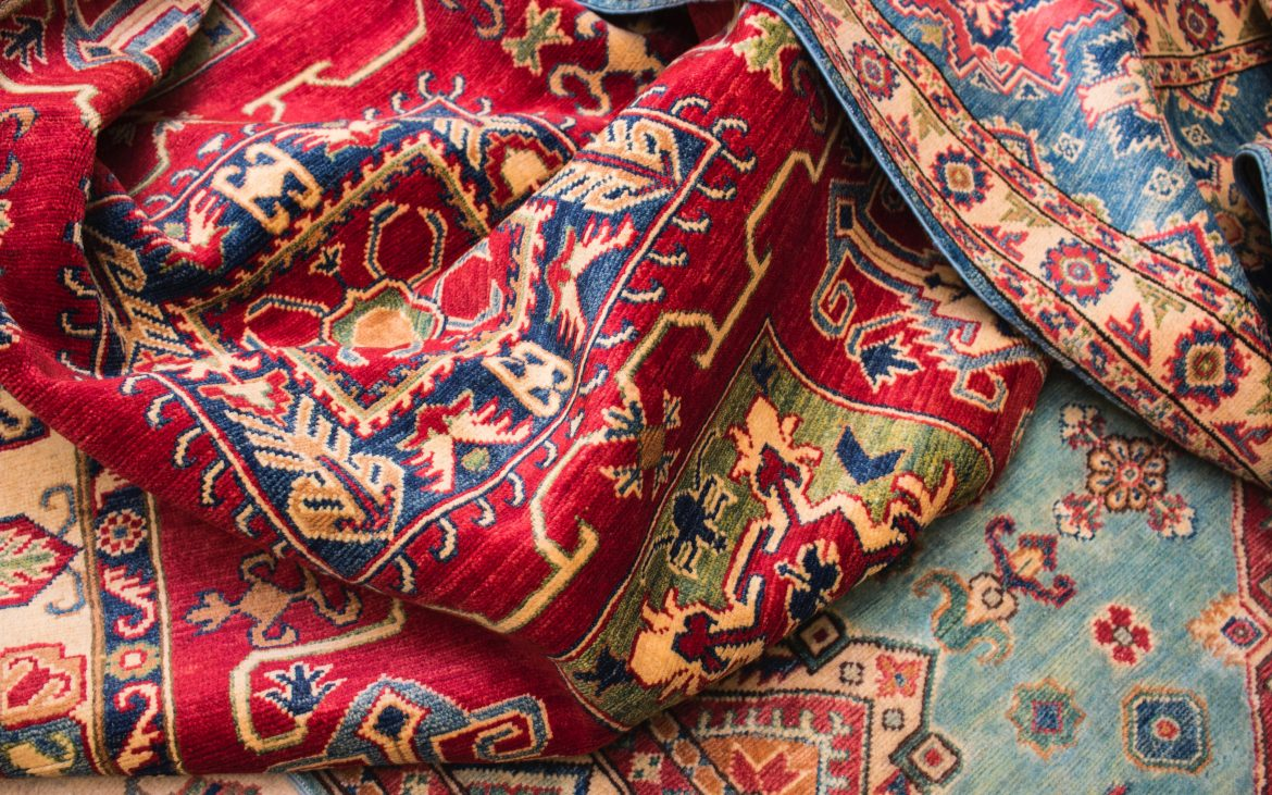 Close up of colorful red, orange and blue design on area rugs