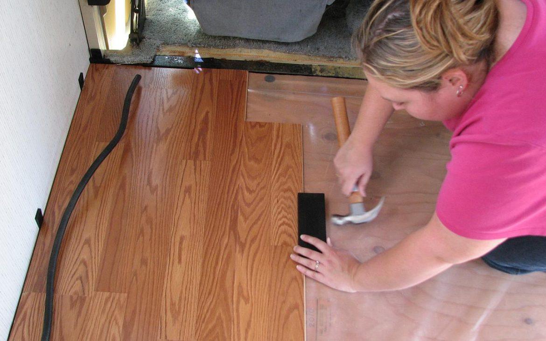 Woman hammering laminate wood floor tiles