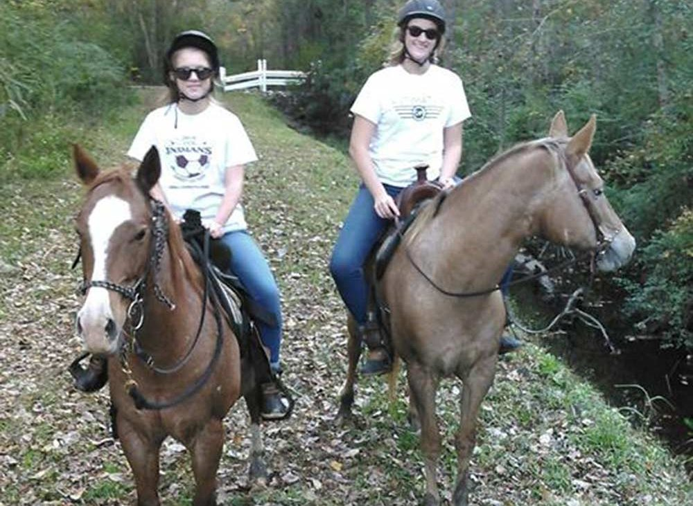 Women on brown horses on dry leave covered trail