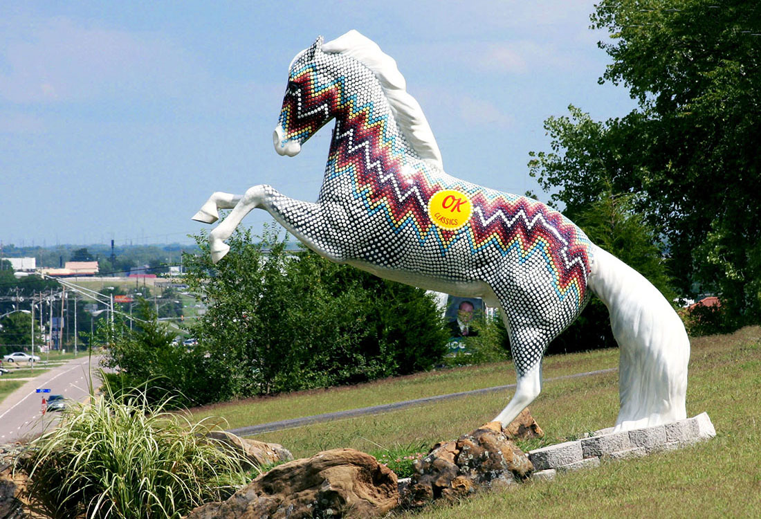 A painted horse sculpture rears on a grassy bank.