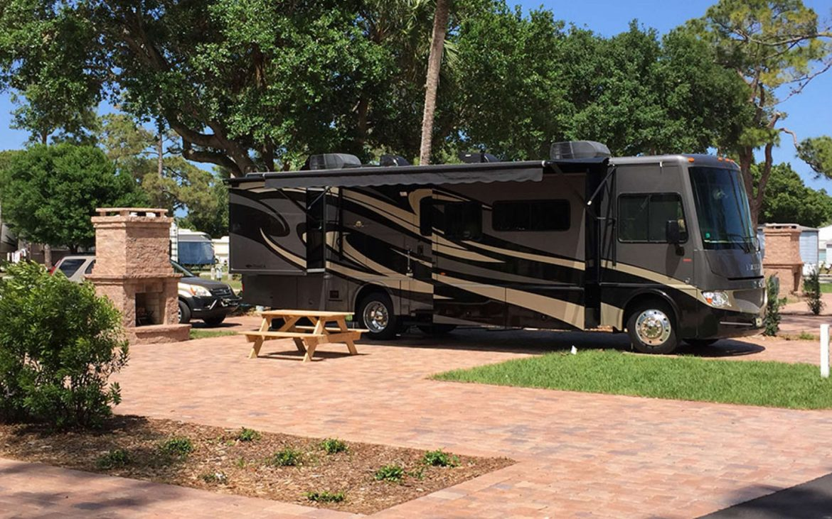 Large black RV parked on red brick path