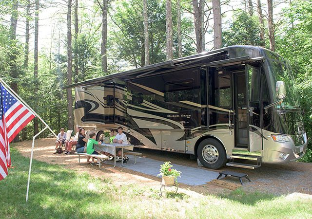 Large tan and brown RV parked along pull-thru