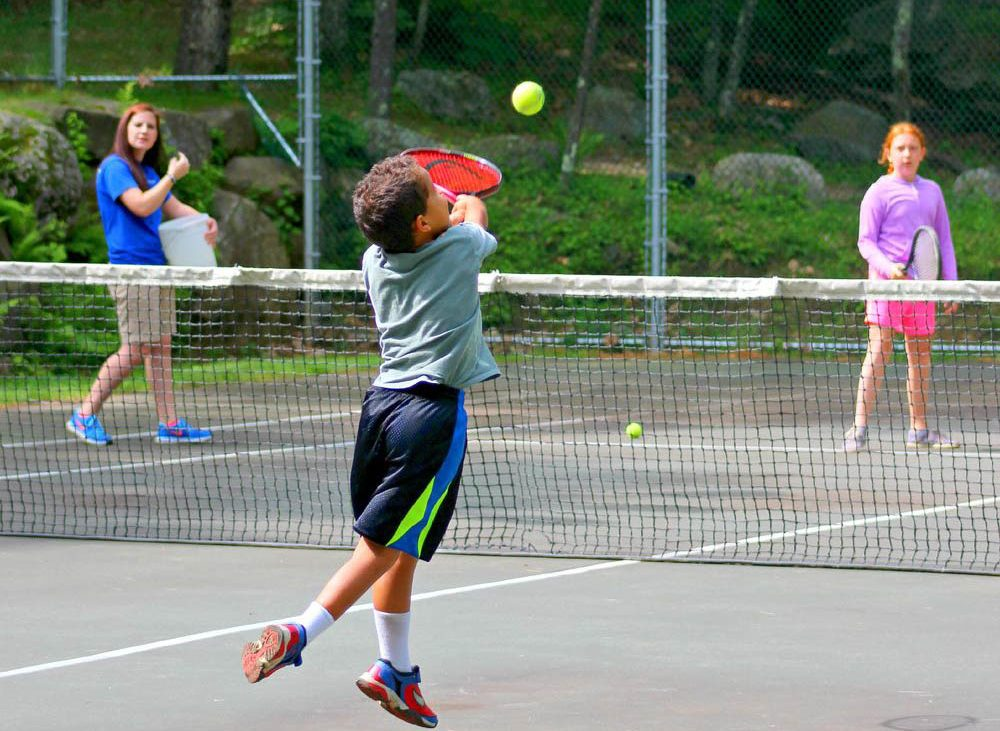 Child playing tennis on crowded court