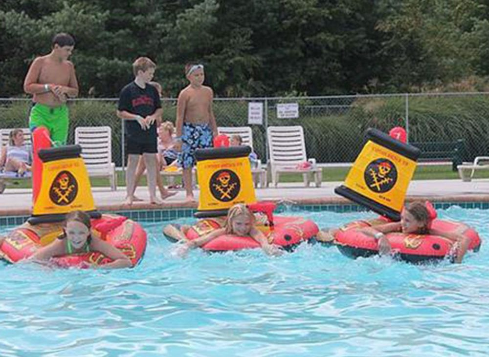 Children playing on red rafts in community pool