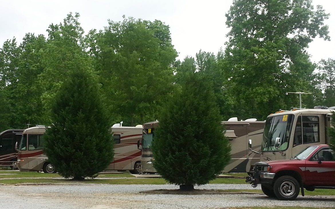 Red truck and RVs parked along gravel road