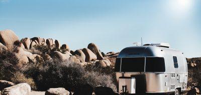 An airstream trailer parked under a hot sun in the desert.