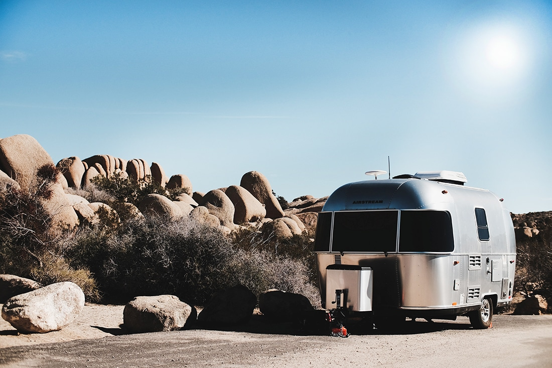 An airstream trailer parked under a hot sun in the desert.