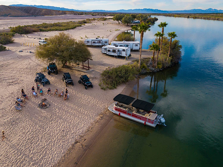 Boats, RVs and off-road vehicles converge on the sandy banks of the Colorado River.