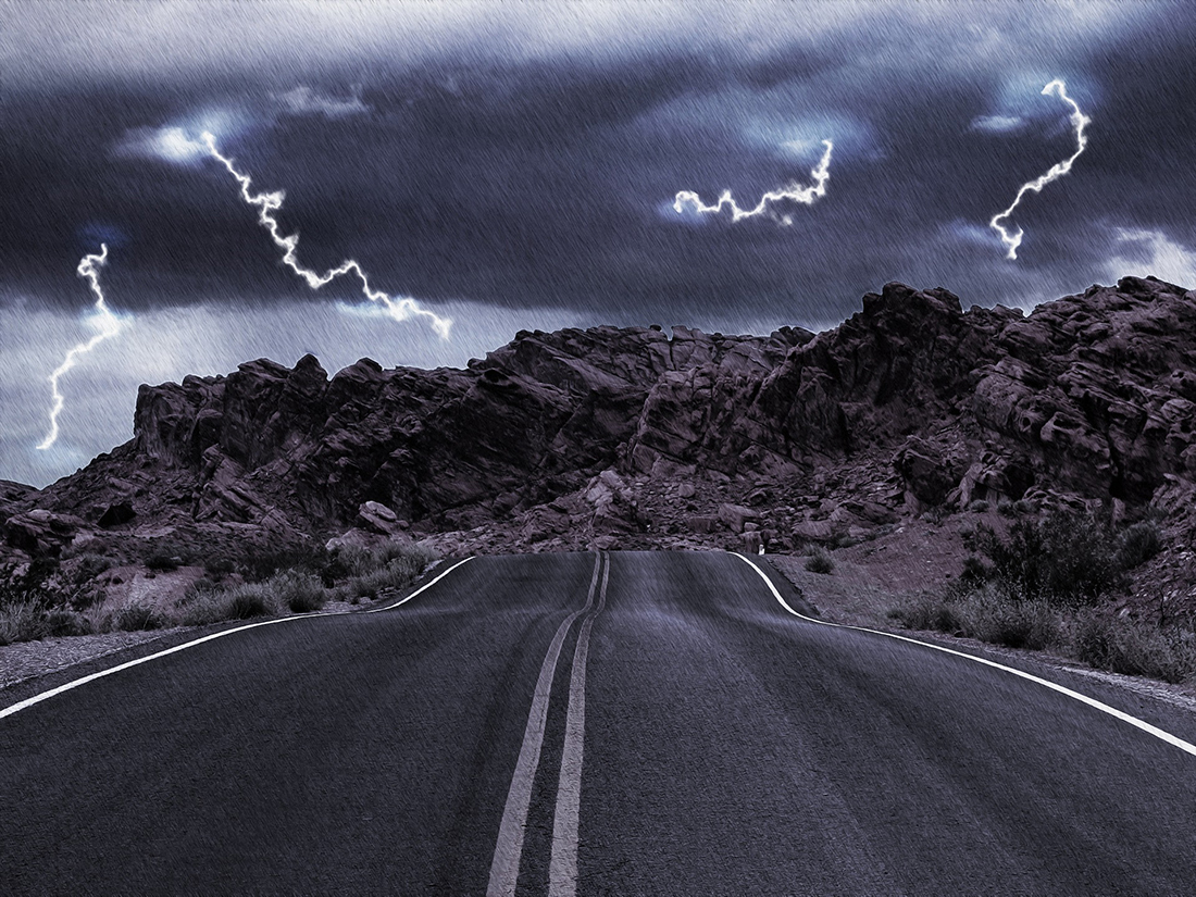 A two-lane road leads to a rocky horizon under flashing thunder.