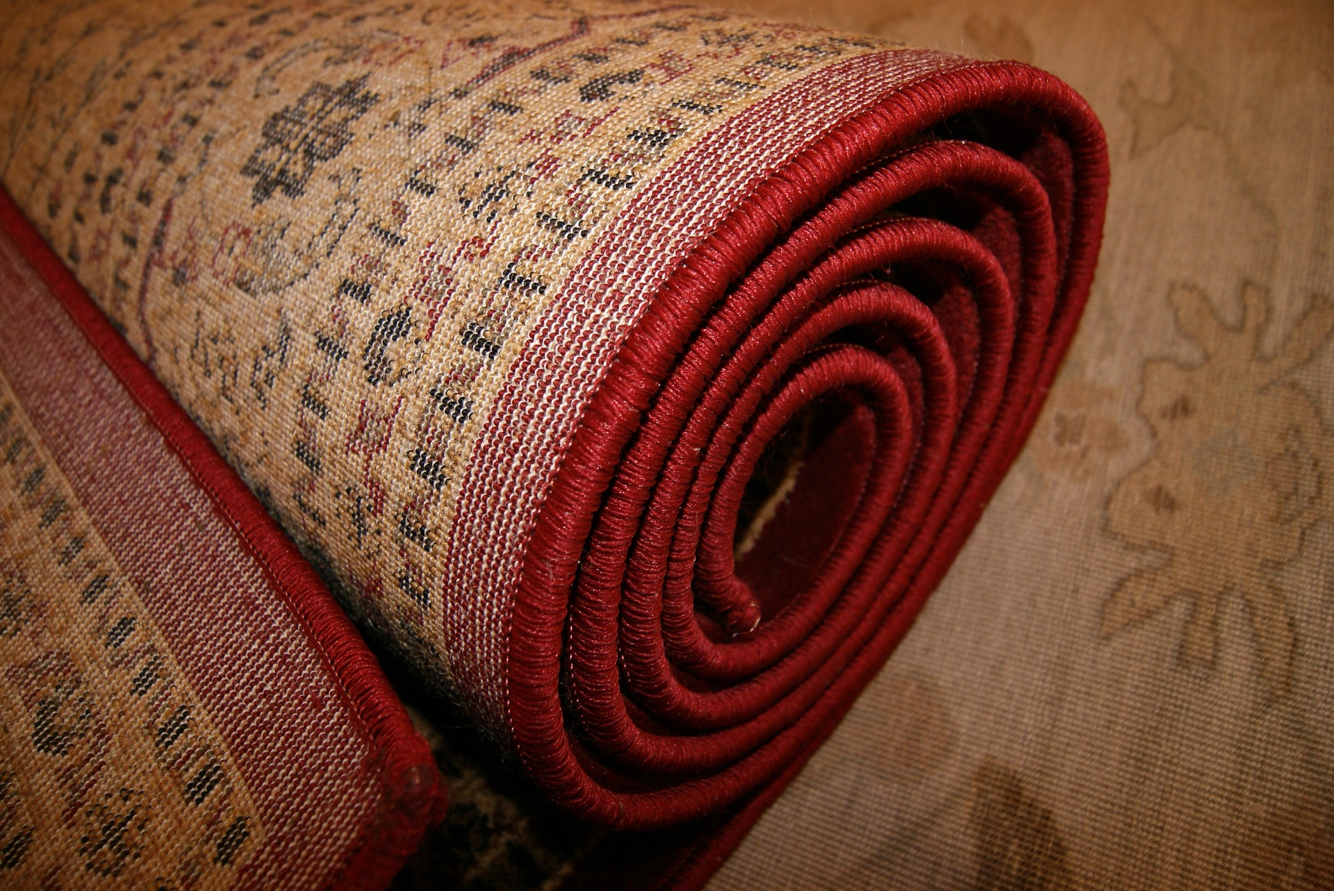 Rolled up red-patterned rug.