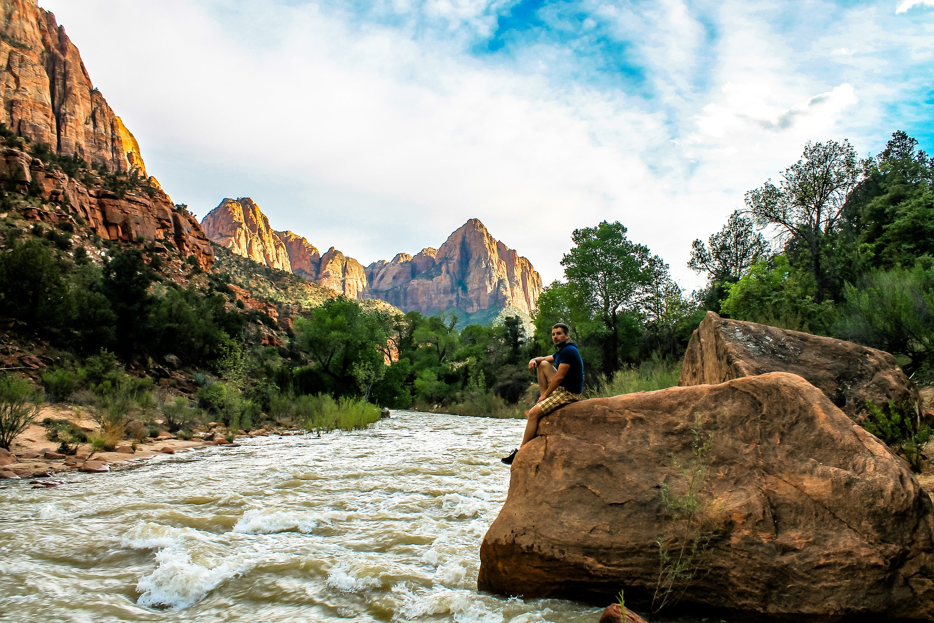 A man relaxes by the foaming Virgin River in Zion National Park.