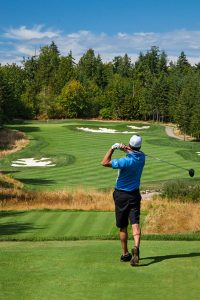 A golfer hits a driver down a green fiarway with bunkers on each side.