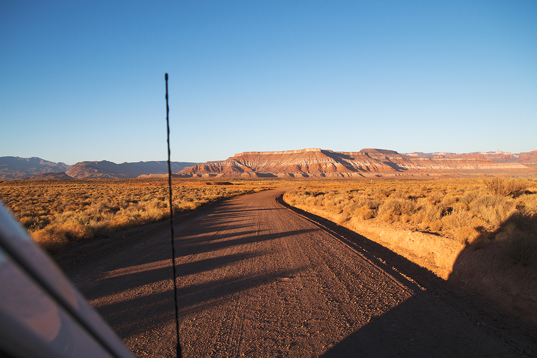 Passenger's view of driving an unpaved road through the desert with bluffs lining the horizon.