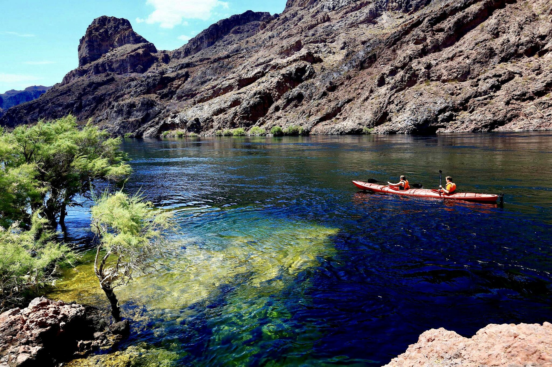 Kayaking on a river with rugged rocky banks.