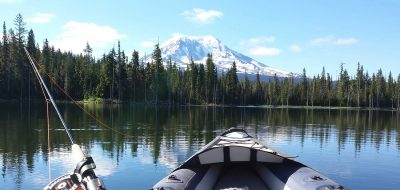 POV from the paddler of an inflatable kayak showing the bow and a fishing pole with mountain in the background.