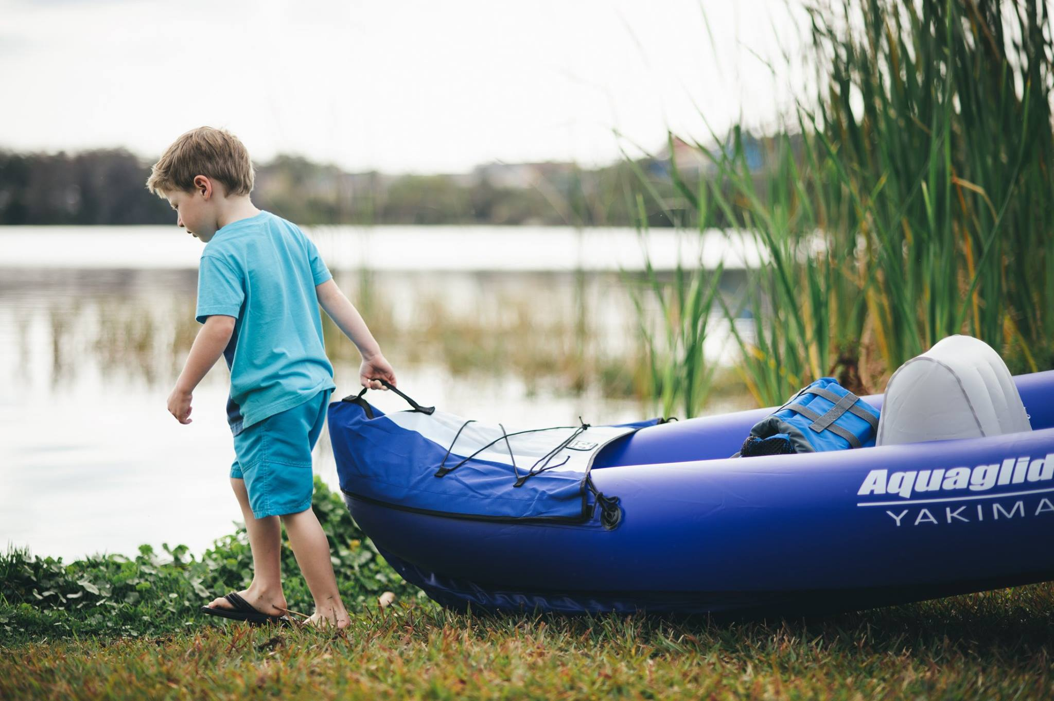 A boy drags an Aquaglide kayak across the grass toward a pond with reeds.