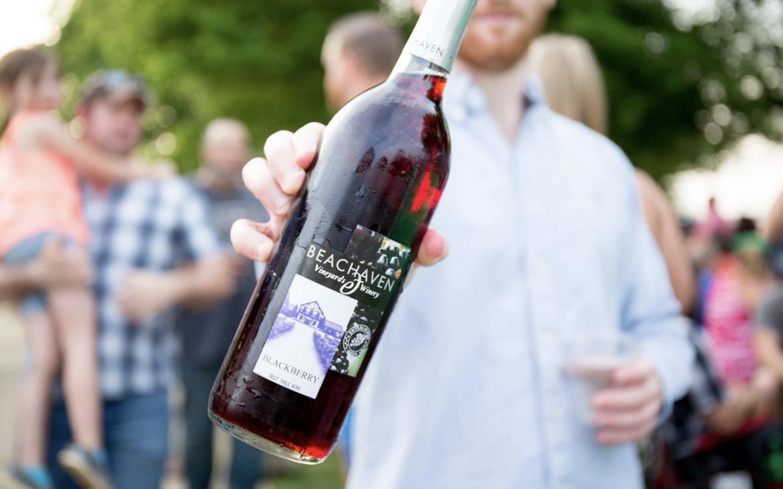 Man holding bottle of red wine towards camera outside