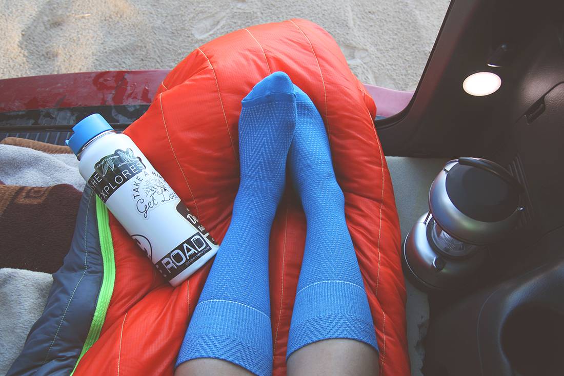 Two feet in blue socks on a sleeping bag in the back seat of a vehicle.