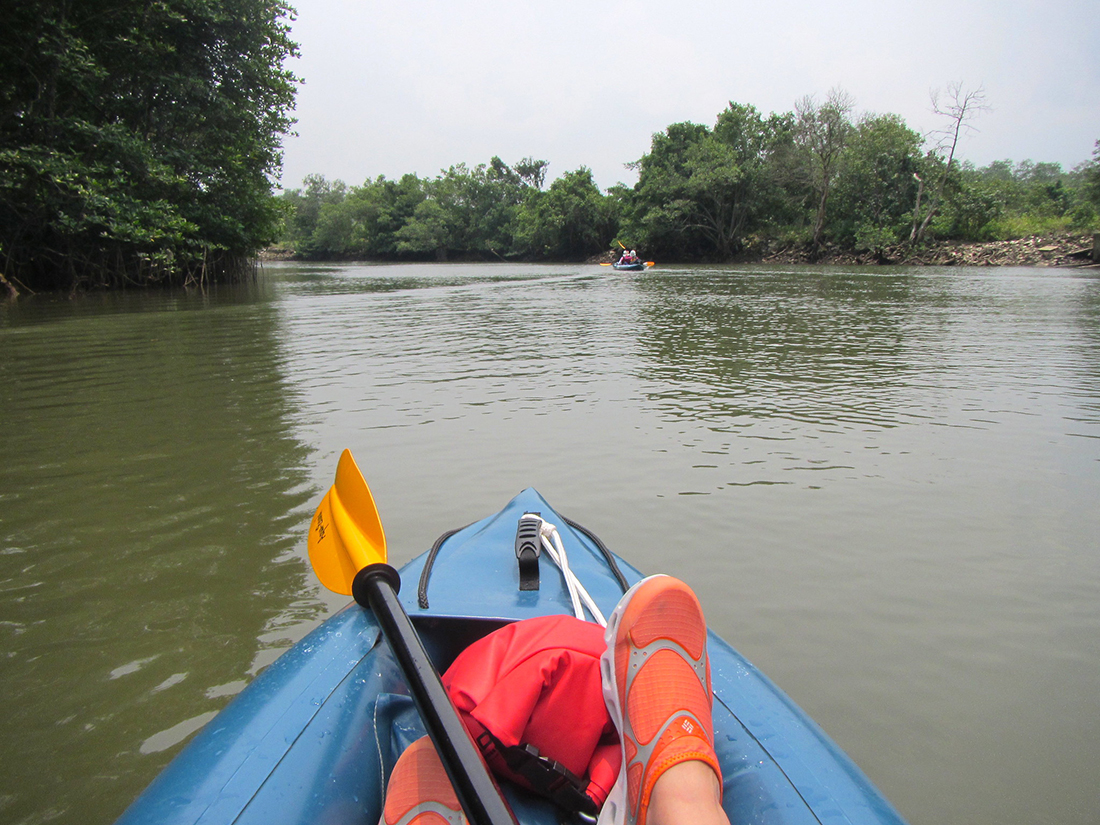 POV from kayak paddler: feet outstretched on muddy stream with paddles placed in resting position.