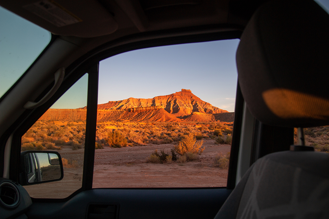 The sunset view of a desert mountain from a vehicle's passenger window.