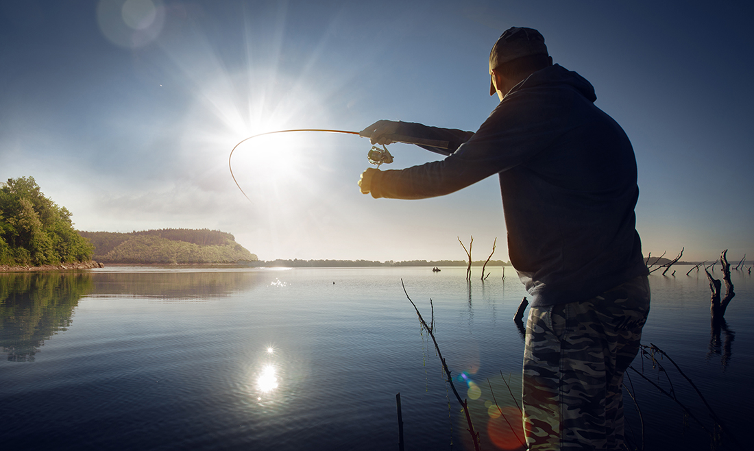 A man wearing a cap casts his line on a lake during sunset.