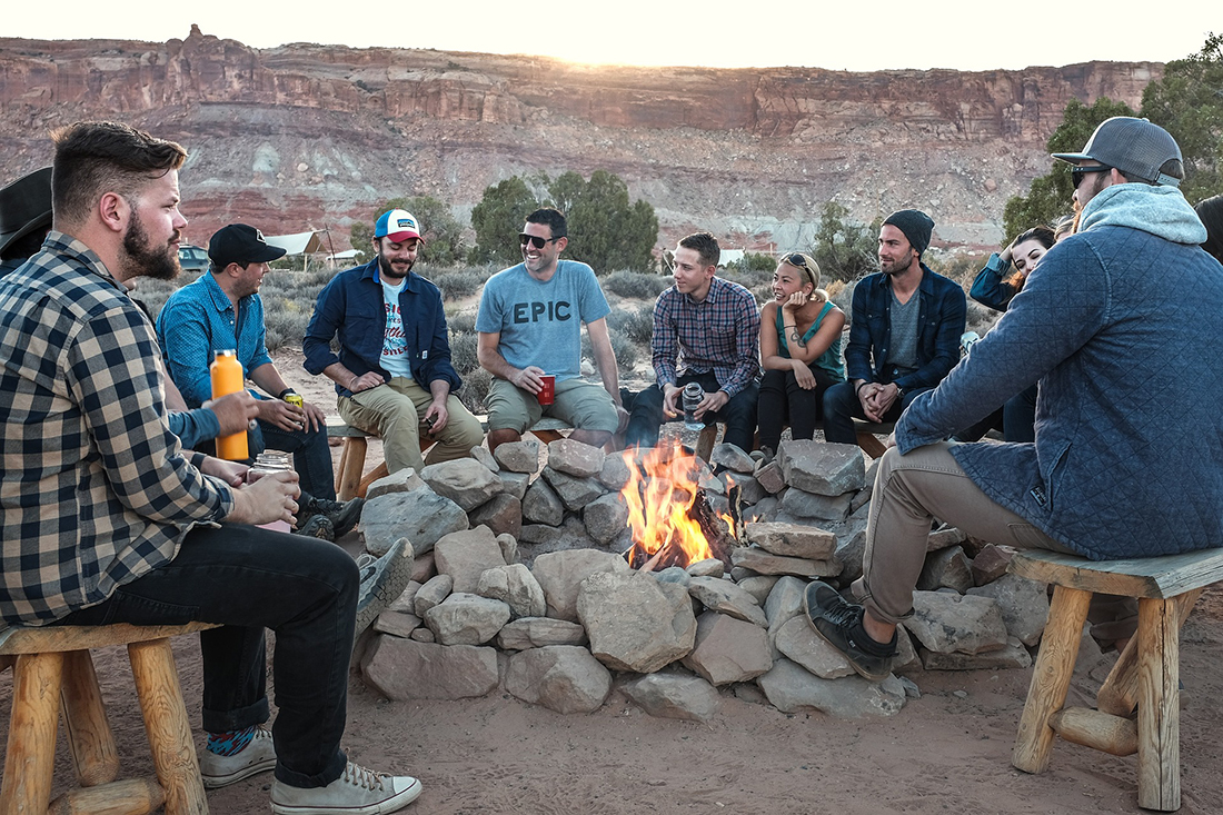 A group of men and women in their 20s and 30s gathered around a campfire at dusk.