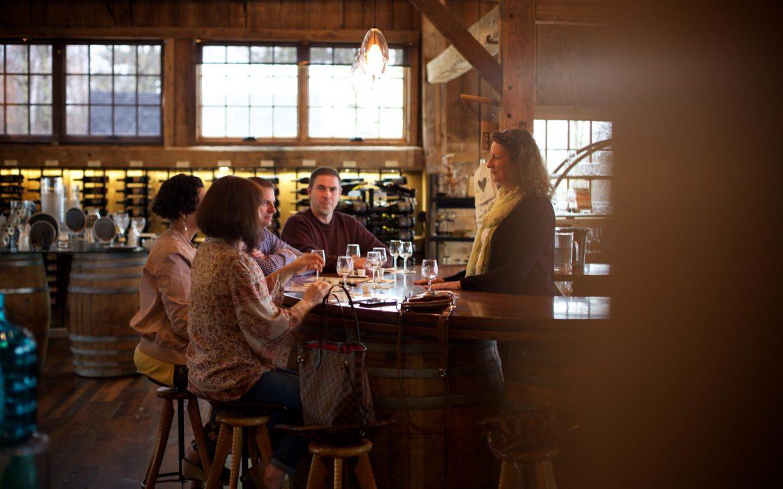 People wine tasting inside at bar