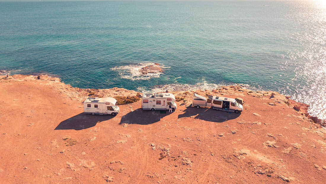 Three Class B RVs parked on a arid bluff overlooking ocean waters.