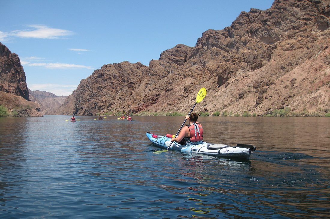 A kayaker knifes through the Colorado River with rocky banks rising on each side.