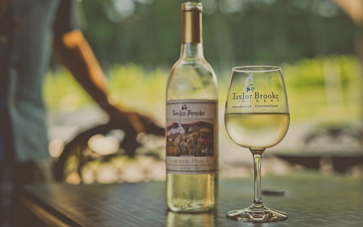 White wine bottle and glass on table outside