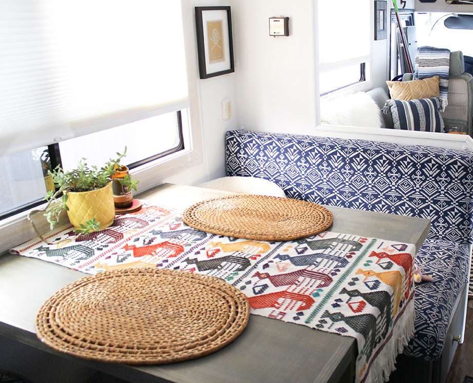 Two placemats and a decorative plant sit on a dinette in a motorhome galley.