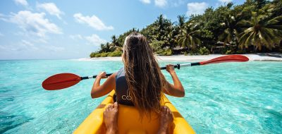 A girl sits in the front of a two-person kayak navigating clear waters in a tropical setting.